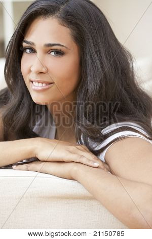 Beautiful Latina Hispanic young woman or girl looking relaxed resting at home on her sofa