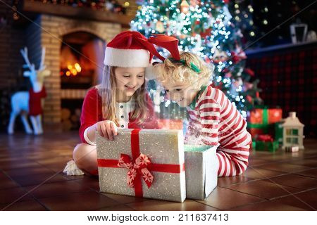 Child At Christmas Tree. Kids At Fireplace On Xmas Poster ID:211637413