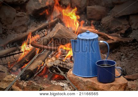 hot dog on a long fork over a fire next to an enamel coffee percolator and mug full of coffee