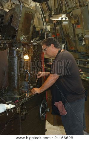 Metal worker in a factory operating a heavy machine