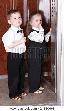 Children in business suit take  elevator. Concept.