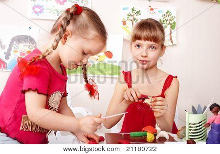 Child  preschooler mould  plasticine in playroom.