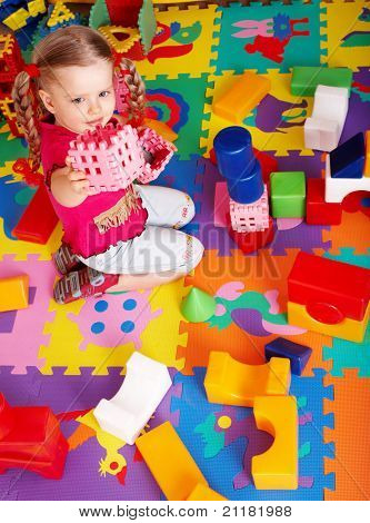 Little girl playing  block and construction set at home.