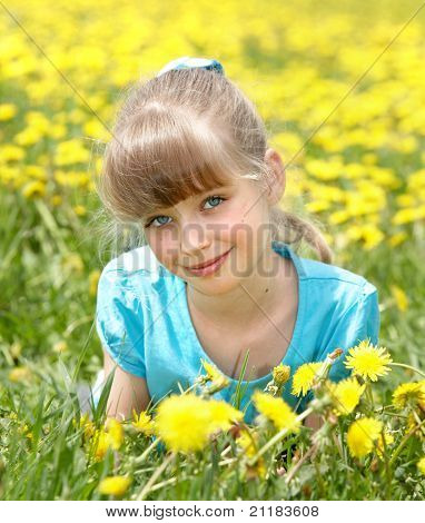 Little girl lying on grass in flower. Outdoor.