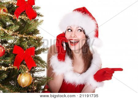 Girl in santa hat call mobile phone by christmas tree. Isolated.