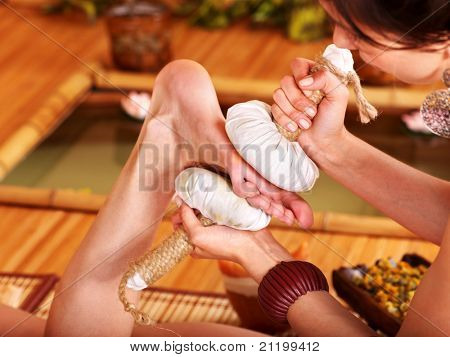 Young woman getting foot massage in bamboo spa.