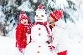 Kids Building Snowman. Children In Snow. Winter Fun. poster