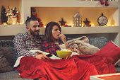 Couple at home eating pop corns while watching movie on tv poster