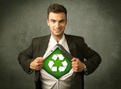 Enviromentalist business man tearing off shirt with recycle sign on his chest concept on backround poster