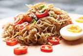 Fried asian instant noodles with egg and vegetables poster