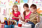 picture of happy kids  - Little girl and boy  painting with teacher in school - JPG