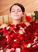 Beautiful young woman in rose petal swim water. Beauty spa.