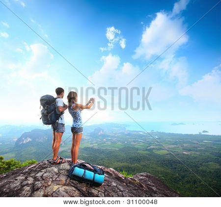 Young tourists with backpacks taking photo of a valley from top of a mountain