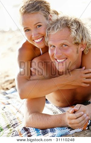 Happy young couple on the beach. Focus on girl.