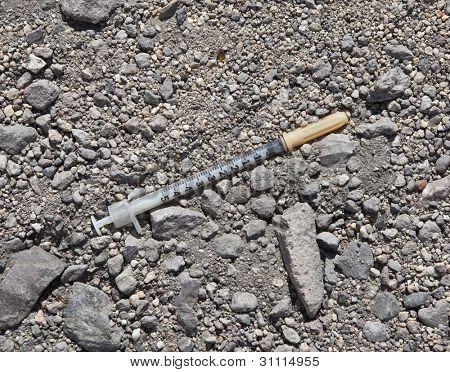 Discarded drug addict needle syringe in the dirt.