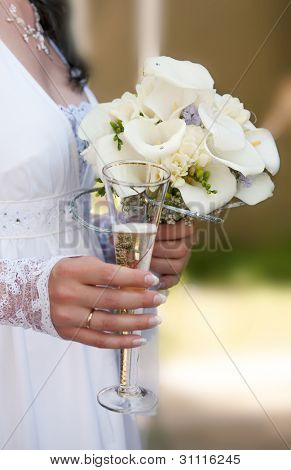 Wedding bouquet and glass with champagne in hands of the bride