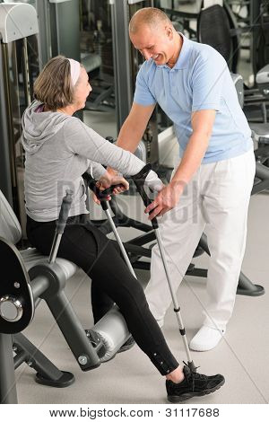 Senior woman with crutches getting help of physiotherapist at gym