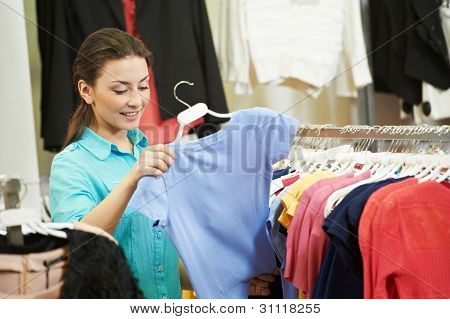 Young woman choosing shirt or blouse during garments clothing shopping at store