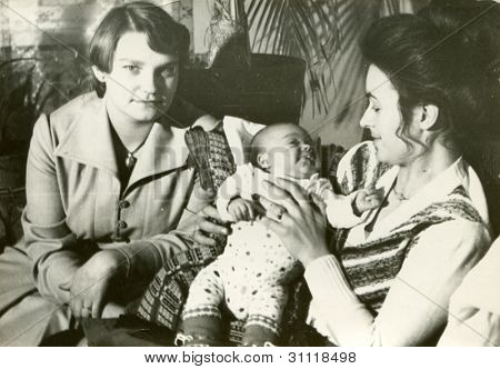Vintage photo of young mother and aunt with a baby boy (early eighties)