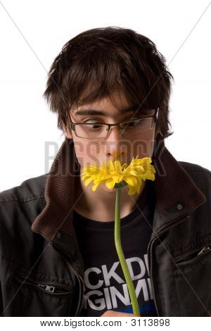 Teenager In Glasses Smelling Yellow Flower