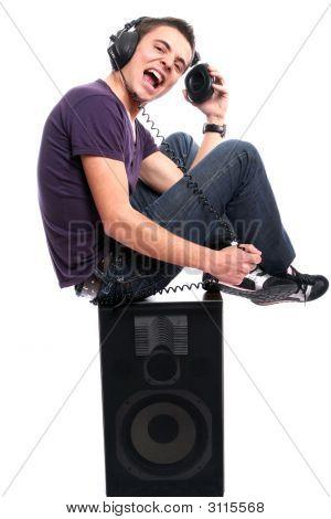 Joven con auriculares, estar en un altavoz