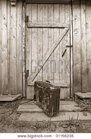 old valise near wooden door, sepia