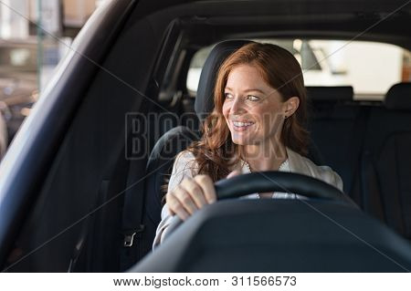poster of Mature beautiful woman sitting in car looking away while trying new automobile. Portrait of daydream