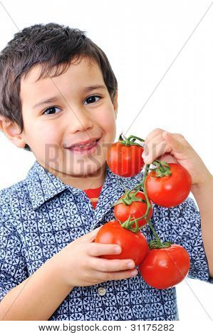Handsome little boy holding tomatoes