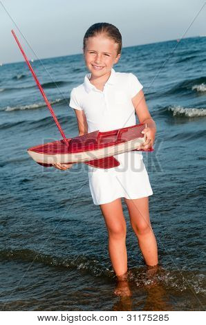 Summer vacation - lovely girl with yacht model on the beach