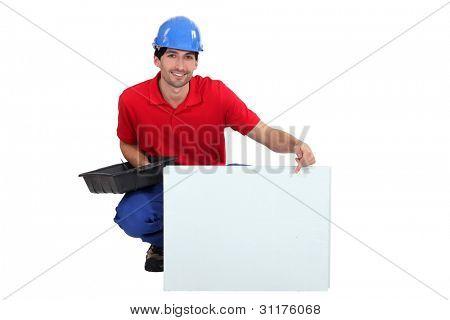 Mason pointint at white panel