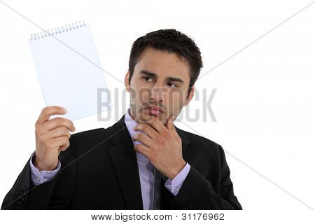 Businessman holding up a blank notepad