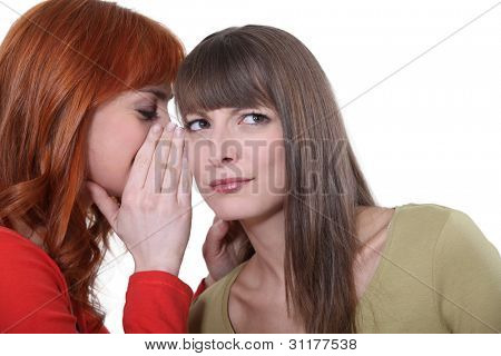 Woman whispering into her friend's ear