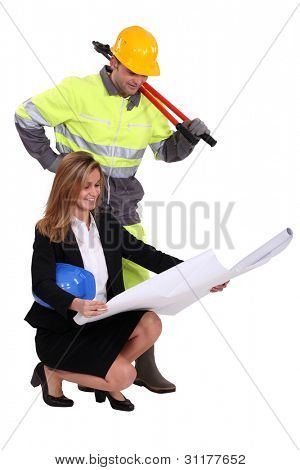 Architect kneeling by builder with plans