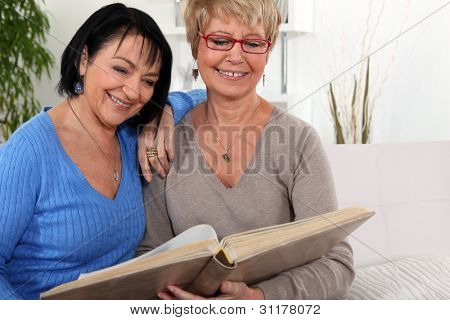 two senior friends looking at a photo album