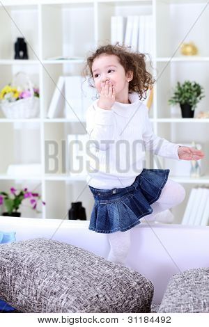 Little girl having fun on sofa in living room, giving kiss