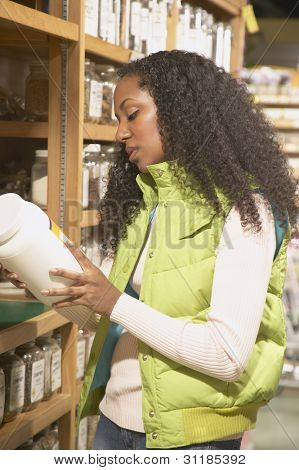 African American woman looking at product in health food store
