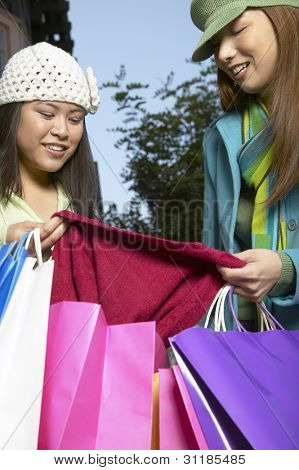 Woman showing female friend her new clothes