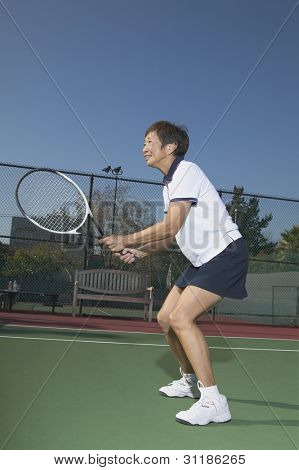 Senior Asian woman playing tennis