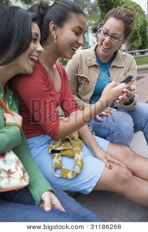 Three girlfriends with mobile phone