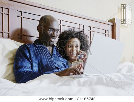 Couple shopping online in bed