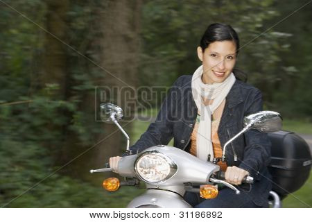 Portrait of woman riding scooter with motion blur