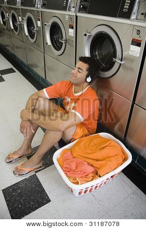Man sitting on floor listening to music in laundromat