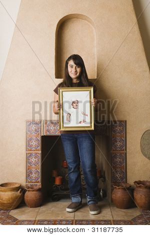 Hispanic teenage girl holding her own baby photograph