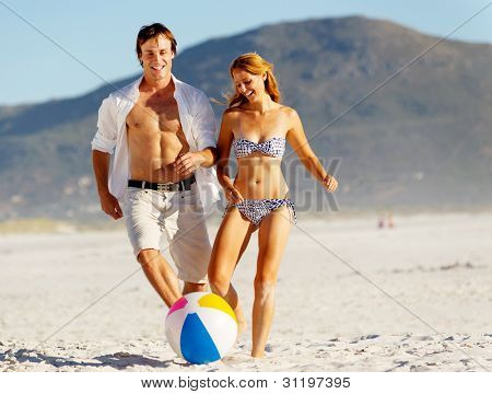 Summer beach couple playing with a beach ball on the sand, laughing and enjoying the sunshine outdoors