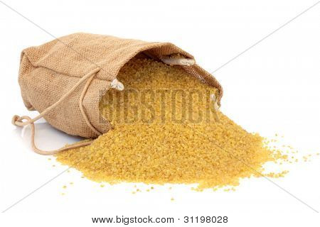 Bulgur wheat in a hessian bag and scattered isolated over white background.