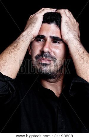 Young hispanic man suffering a headache or a very strong stress or depression isolated on black