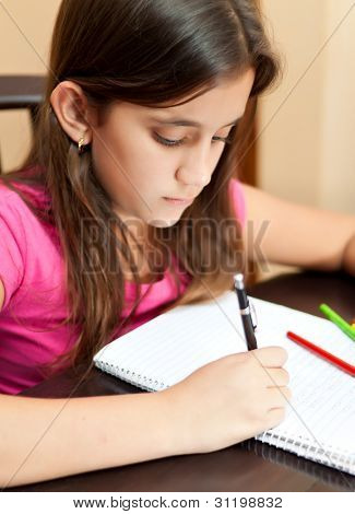 Vertical portrait of a beautiful latin girl working on her school homework