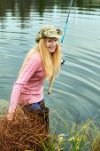 picture of fisherwomen  - beautiful blond girl fishing in pond at autumn