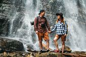 Man And Woman Hikers Trekking A Rocky Path Against The Background Of A Waterfall And Rocks. Hiker Co poster