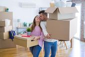 Young beautiful couple in love moving to new home, holding cardboard boxes very happy and cheerful f poster
